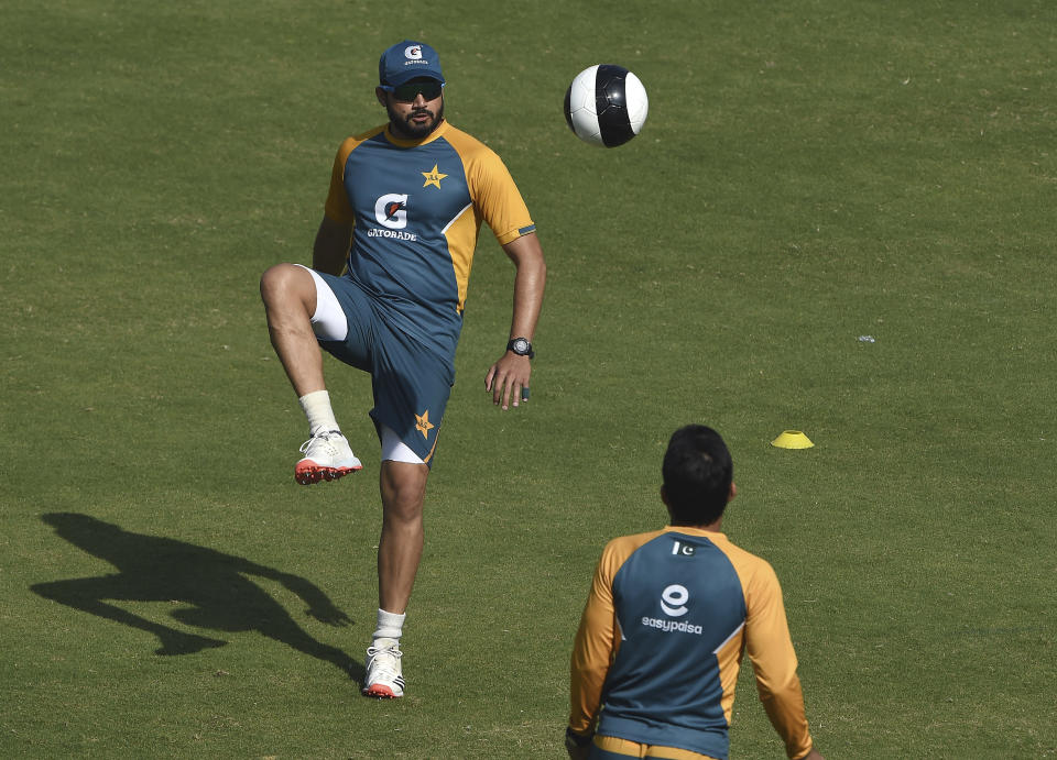 Pakistan's Azhar Ali, center, kicks a soccer ball during a practice session at National Stadium in Karachi, Pakistan, Monday, Jan. 25, 2021. Pakistan will play the first test match against South Africa on Jan. 26. (AP Photo/Fareed Khan)