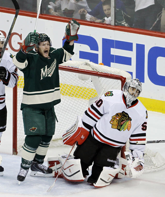 Minnesota Wild left wing Matt Cooke, left, celebrates after Wild right wing Justin Fontaine scored on Chicago Blackhawks goalie Corey Crawford, right, during the first period of Game 4 of an NHL hockey second-round playoff series in St. Paul, Minn., Friday, May 9, 2014. (AP Photo/Ann Heisenfelt)