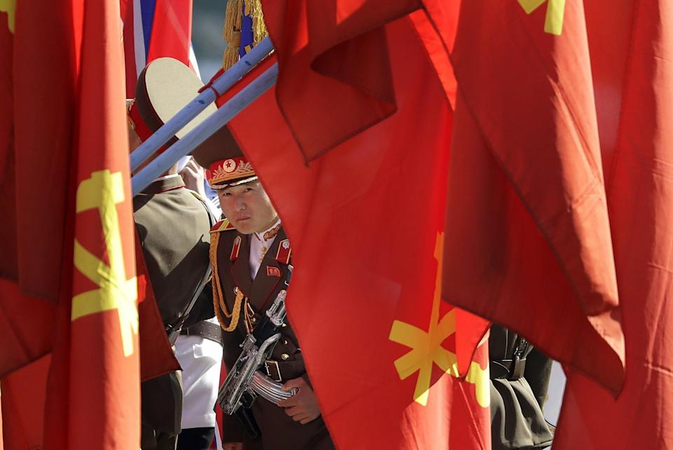 <p>A North Korean military soldier peeps through his country's ruling party flags decorating the Ryomyong residential area, a collection of more than a dozen apartment buildings, ahead of its official opening ceremony. (AP Images) </p>