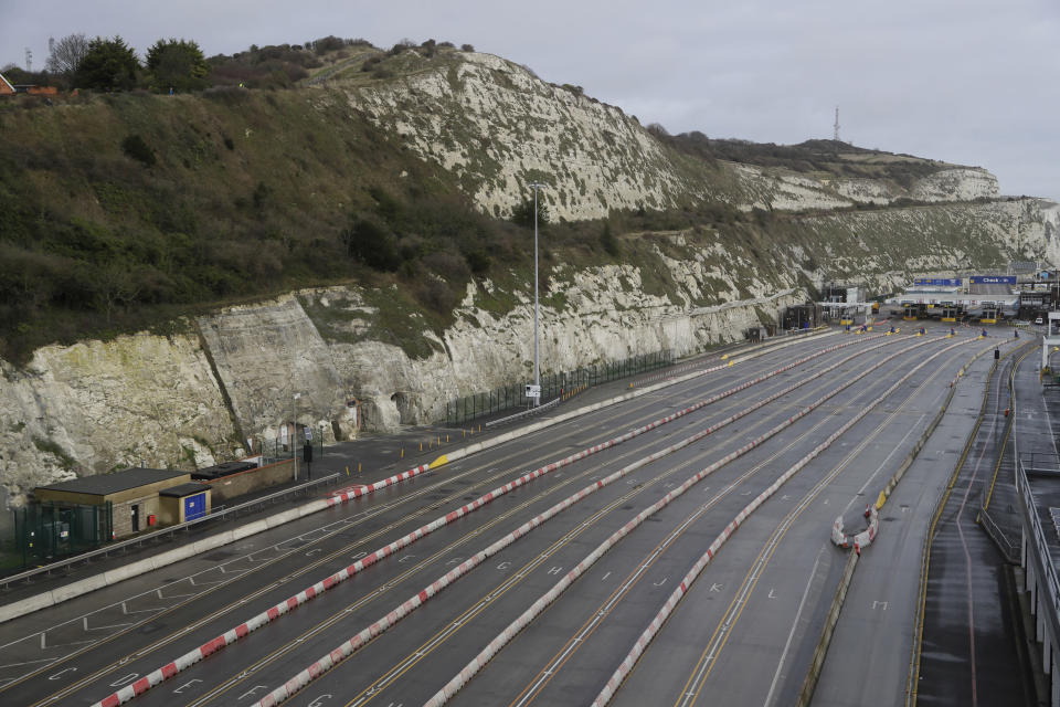FILE - In this Tuesday, Dec. 22, 2020 file photo the ferry terminal check-in is empty alongside the White Cliffs of Dover, whilst the Port remains closed, in Dover, southern England. Trucks waiting to get out of Britain backed up for miles and people were left stranded at airports as dozens of countries around the world slapped tough travel restrictions on the U.K. because of a new and seemingly more contagious strain of the coronavirus in England. (AP Photo/Kirsty Wigglesworth, File)