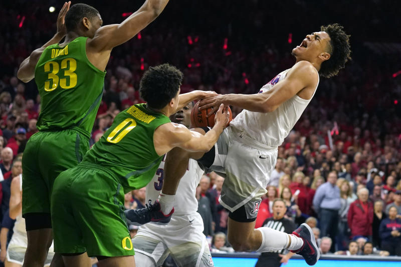 Arizona guard Josh Green, right, is fouled as Oregon's Will Richardson (0) and Francis Okoro (33) defend during the second half of an NCAA college basketball game Saturday, Feb. 22, 2020, in Tucson, Ariz. Oregon won 73-72 in overtime. (AP Photo/Rick Scuteri)