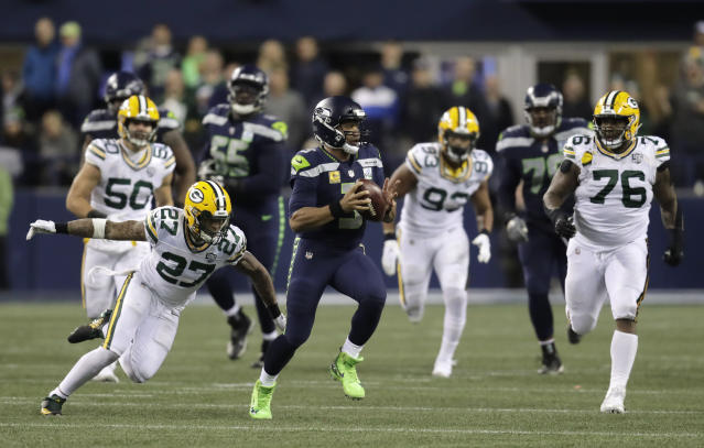 Seattle Seahawks quarterback Russell Wilson (3) scrambles away from Green Bay Packers defensive back Josh Jones (27) during the first half of an NFL football game Thursday, Nov. 15, 2018, in Seattle. (AP Photo/Stephen Brashear)