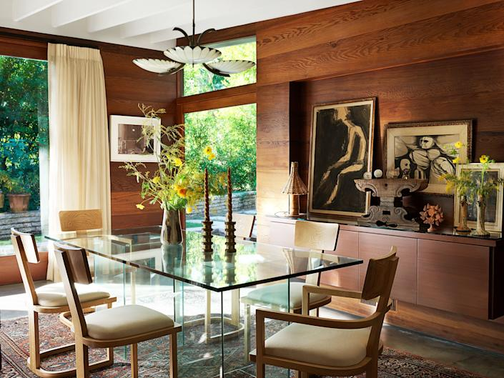 A French art deco pendant hangs over the custom dining table with chairs by Nickey Kehoe. Art (left) by Faris McReynolds.