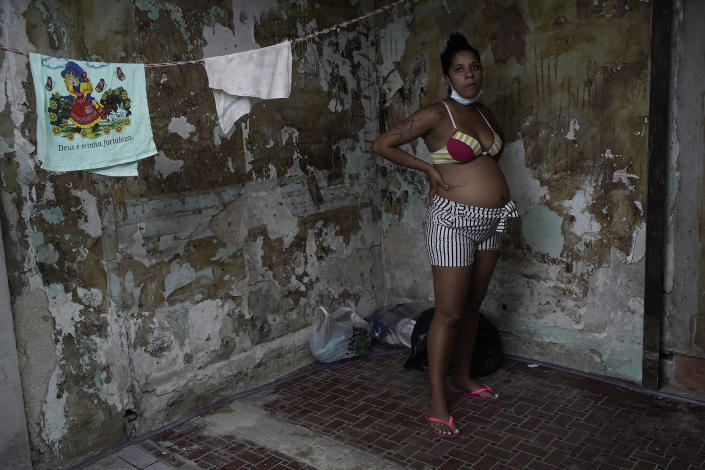 """Actress Kelly Regina da Silva, who before the pandemic hit had made it out of her working-class slum, poses for a photo in the building where she now lives in a small room in one of the city center's squats, in Rio de Janeiro, Brazil, Tuesday, March 16, 2021. Even among the world's richest nations, a PricewaterhouseCoopers survey this month found COVID-19 threatened to reverse the important gains women made over the last decade with """"lasting, or even permanent"""" damage. (AP Photo/Silvia Izquierdo)"""