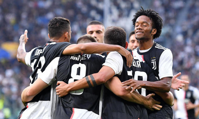 Juventus' Aaron Ramsey, second from left, celebrates with his teammates after scoring his side first goal during the italian Serie A soccer match between Juventus and Verona at the Juventus' Stadium in Turin, Italy, Saturday, Sept. 21, 2019. (Alessandro Di Marco/ANSA via AP)