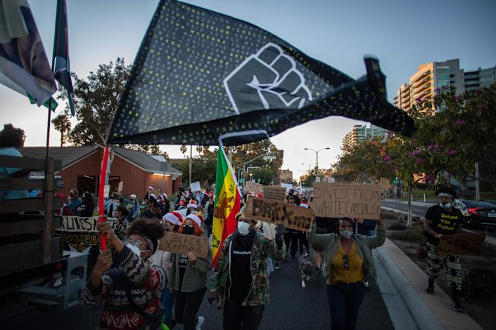 <p>Protesters march through the Marina Del Rey neighbourhood of Los Angeles during a Black Lives Matter rally to demand social justice on December 19, 2020</p> (AFP via Getty Images)