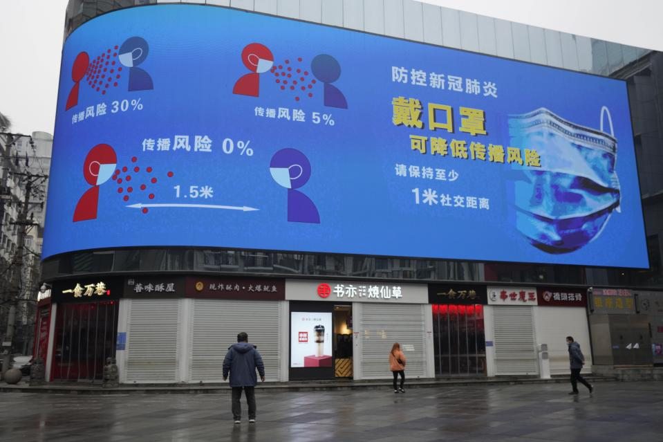 A man looks on near a giant display advocating the effectiveness of wearing masks to curb the spread of the coronavirus ahead of the anniversary of the 76-day lockdown of the city where the coronavirus was first detected in Wuhan in central China's Hubei province on Friday, Jan. 22, 2021. (AP Photo/Ng Han Guan)