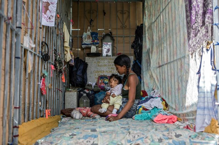 A young woman and her baby sit in a makeshift hut amongst tombstones in Caracas