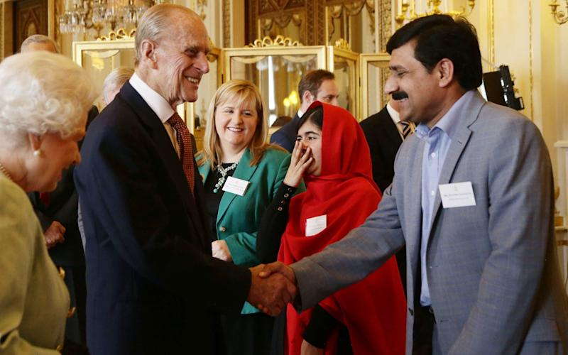 Malala Yousafzai reacts to a comment made by the Duke of Edinburgh, as he greets her father Ziauddin, during a Reception for Youth, Education and the Commonwealth at Buckingham Palace in 2013 - Credit: Yui Mok/PA