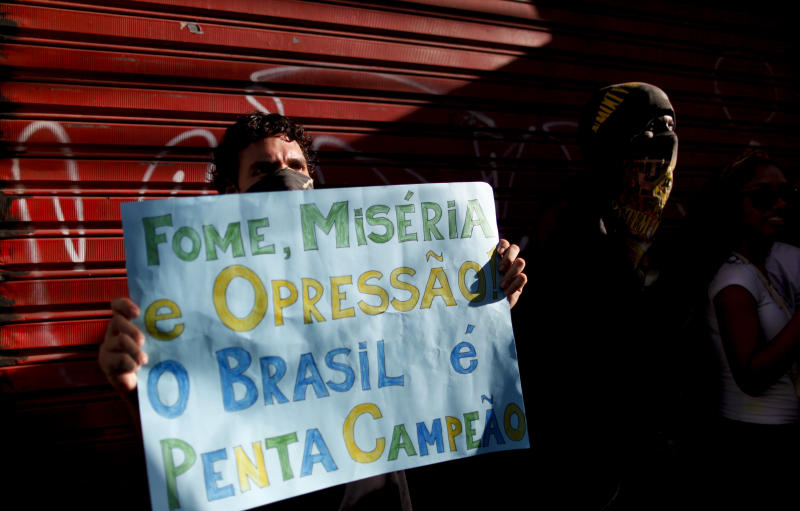 "A protester holds a sign that reads in Portuguese ""Hunger, misery and oppression and Brazil five time champions,"" a few miles from the soccer stadium where Nigeria and Uruguay will play in a Confederations Cup soccer game in Salvador, Brazil, Thursday, June 20, 2013. Beginning as protests against bus fare hikes, demonstrations have quickly ballooned to include broad middle-class outrage over the failure of governments to provide basic services and ensure public safety. (AP Photo/Natacha Pisarenko)"