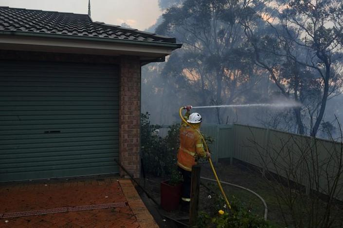 NSW Rural Fire Service personnel conducts property protection as a bushfire burns in Woodford NSW
