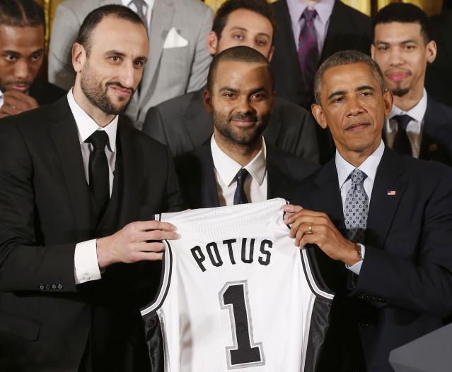 U.S. President Barack Obama poses for a team photo next to players Manu Ginobili (L) and Tony Parker (C) while holding a team jersey as he welcomes the 2014 NBA Champion San Antonio Spurs to the East Room of the White House in Washington, January 12, 2015. REUTERS/Larry Downing (UNITED STATES - Tags: POLITICS SPORT BASKETBALL)