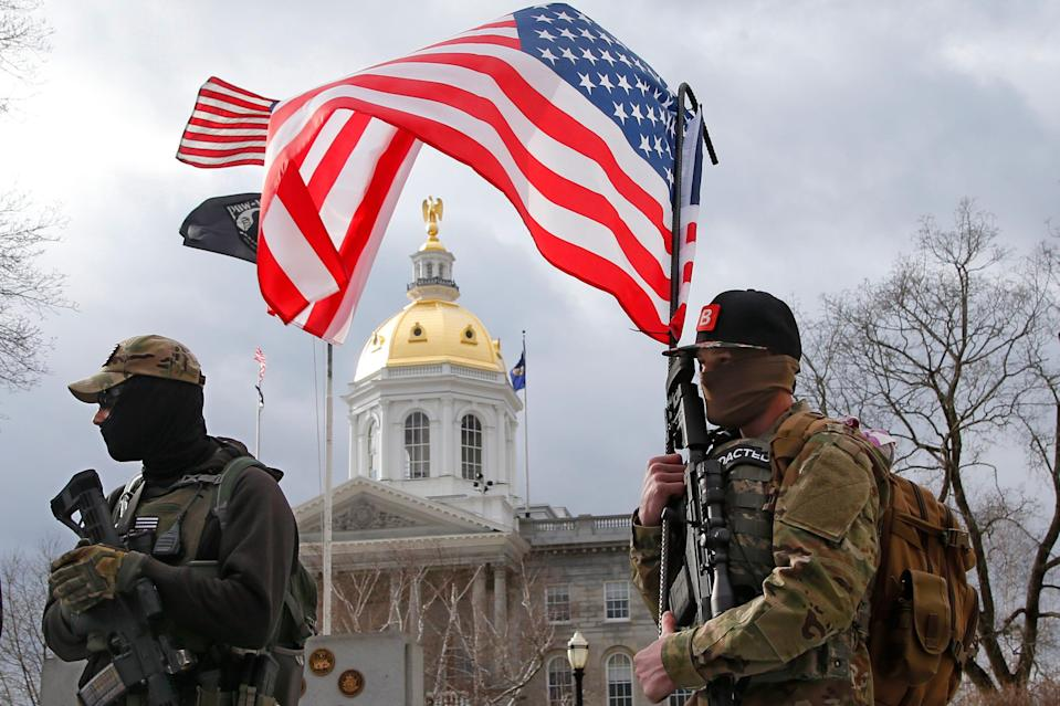 Armed protesters stand in front of the Statehouse on Sunday, Jan. 17, 2021, in Concord, N.H.