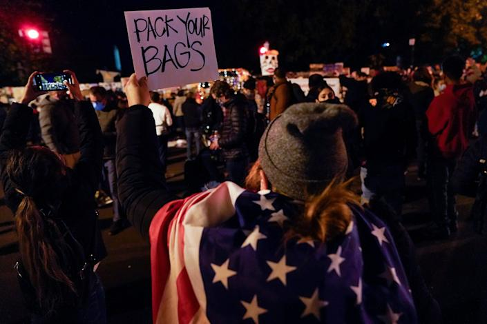 A demonstrator holds up a sign while watching election returns outside the White House, Tuesday, Nov. 3, 2020, in Washington.