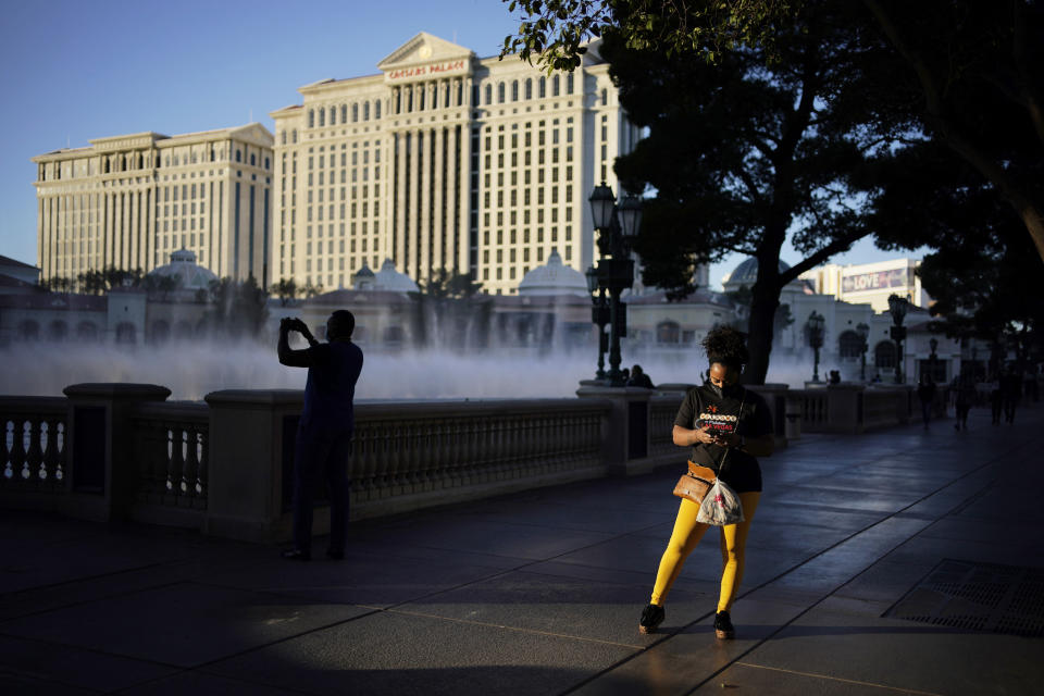 People walk along the Las Vegas Strip, Thursday, Nov. 19, 2020, in Las Vegas. As the coronavirus surges to record levels in Nevada, the governor has implored residents to stay home. But Democrat Steve Sisolak has also encouraged out-of-state visitors, the lifeblood of Nevada's limping economy, to come to his state and spend money in Las Vegas. (AP Photo/John Locher)
