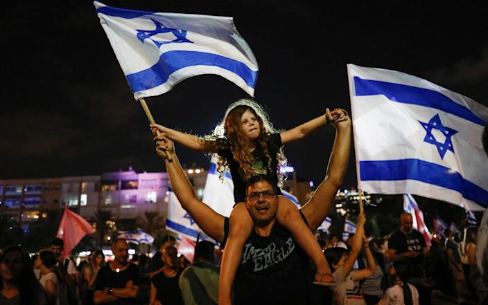 People celebrate in Tel Aviv after Israel's parliament voted in a new coalition government, initially to be headed up by Naftali Bennett - CORINNA KERN/REUTERS