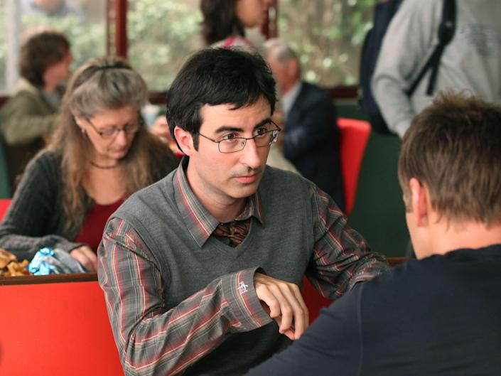 """John Oliver as Professor Ian Duncan sits at a cafeteria table in """"Community."""""""