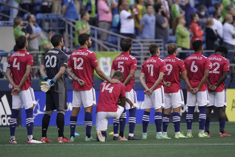 FC Dallas defender Nkosi Burgess (14) kneels during the singing of the national anthem before the team's MLS soccer match against the Seattle Sounders, Wednesday, Aug. 4, 2021, in Seattle. (AP Photo/Ted S. Warren)