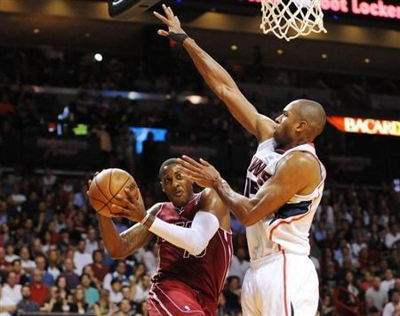 Dec 23, 2013; Miami, FL, USA; Miami Heat point guard Mario Chalmers (15) is defended by Atlanta Hawks center Al Horford (15) under the basket during the second half at American Airlines Arena. The Heat won 121-119 in overtime. Mandatory Credit: Steve Mitchell-USA TODAY Sports