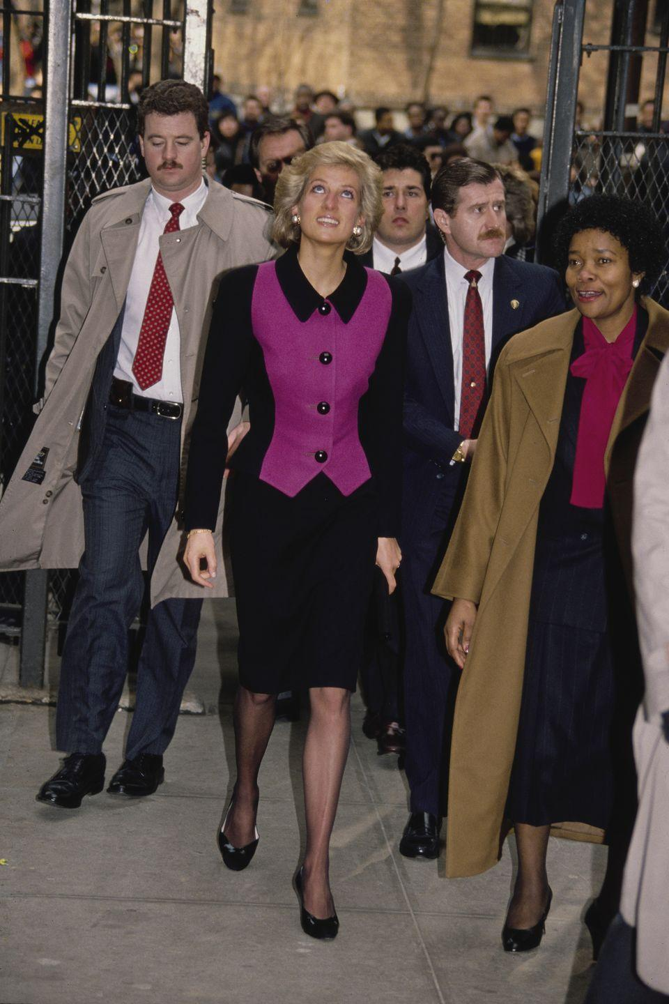 <p>Diana wears a pink and black, colorblocked suit by Catherine Walker. </p>