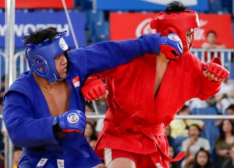 Singapore's Nazri Sutari (left) lands a punch on Indonesia's Jason Sim en route to winning gold in the men's combat sambo U-82kg. (PHOTO: Sport Singapore)