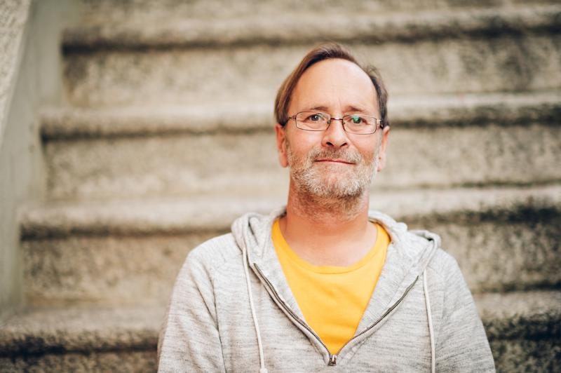 Middle-aged man sitting on stairs wearing gray sweatshirt over yellow t-shirt