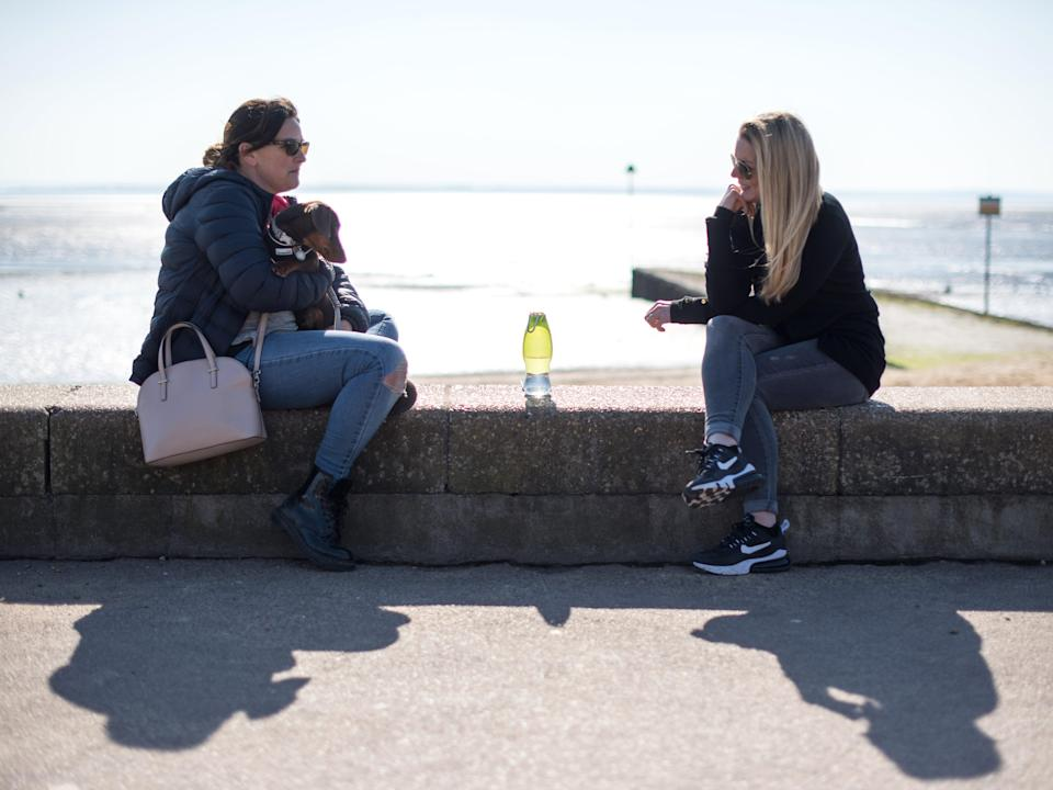 Two friends from different households meet for a chat on Chalkwell beach on March 9, 2021 in Southend-on-Sea, England (Getty Images)