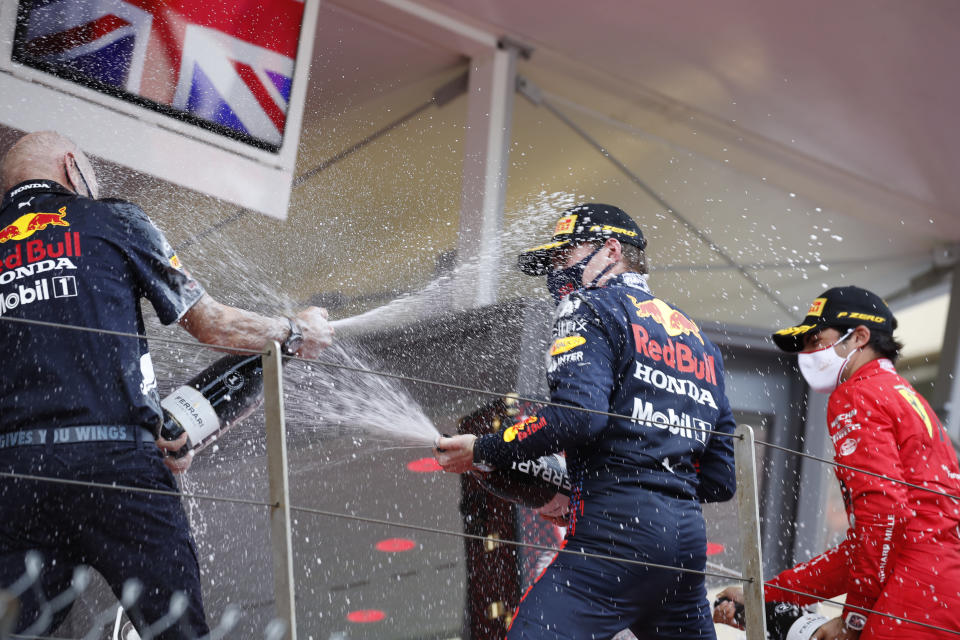 First place Red Bull driver Max Verstappen of the Netherlands, center, and second place Ferrari driver Carlos Sainz of Spain, right, celebrate on the podium during the Monaco Grand Prix at the Monaco racetrack, in Monaco, Sunday, May 23, 2021. (Sebastien Nogier, Pool via AP)