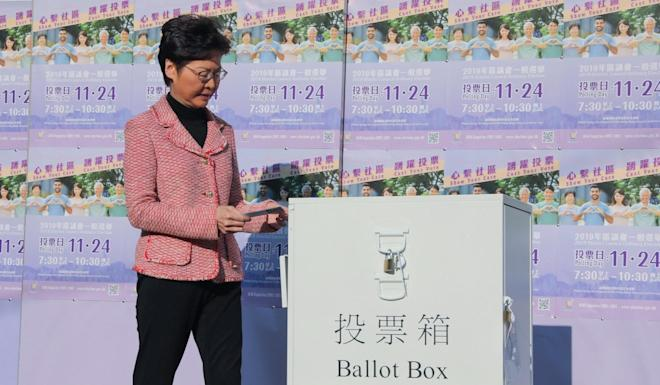 Carrie Lam casts her vote at Raimondi College before appealing for the relative calm in the city to continue after the elections. Photo: K. Y. Cheng