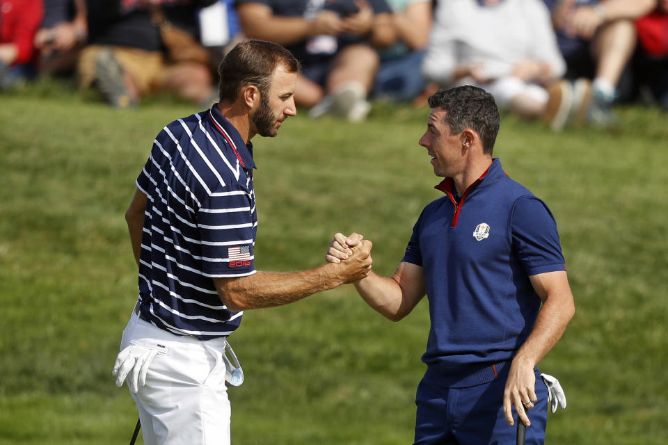 FILE - In this Sept. 28, 2018, file photo, Dustin Johnson left, and Rory McIlroy shake hands on 16th green at the end of a fourball match on the opening day of the 42nd Ryder Cup in Saint-Quentin-en-Yvelines, outside Paris, France. Johnson and McIlroy headline a $3 million charity match for COVID-19 relief that will mark the first live golf on television since the pandemic shut down sports worldwide. The May 17 match will be played at Seminole Golf Club in South Florida. (AP Photo/Alastair Grant, File)