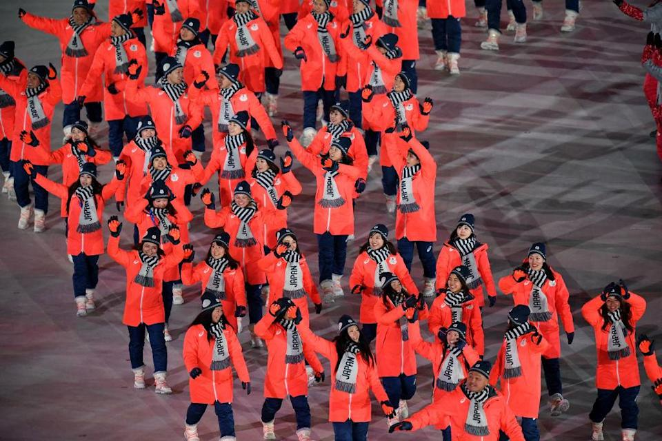 "<p>Flag bearer Sara Takanashi of Japan and teammates wear red zip jackets, navy pants, and ""Japan"" gray scarves when entering the stadium during the opening ceremony of the 2018 PyeongChang Games. (Photo: Pool — Frank Fife/Getty Images) </p>"