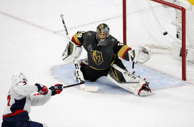 Vegas Golden Knights goaltender Marc-Andre Fleury, right, deflects a shot by Washington Capitals left wing Jakub Vrana, of the Czech Republic, during the second period in Game 2 of the NHL hockey Stanley Cup Finals on Wednesday, May 30, 2018, in Las Vegas. (AP Photo/Ross D. Franklin)