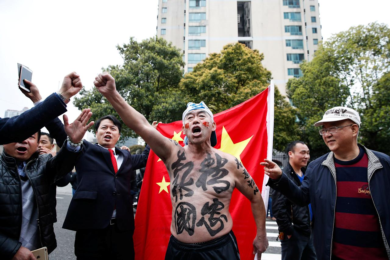 "Supporters of the Chinese national team chant slogans outside Helong Stadium ahead of a 2018 FIFA World Cup qualifier match between China and South Korea in Changsha, Hunan province, China, March 23, 2017. The Chinese characters on the body of the man read, ""Supreme loyalty to serve the country."" REUTERS/Stringer ATTENTION EDITORS - THIS IMAGE WAS PROVIDED BY A THIRD PARTY. EDITORIAL USE ONLY. CHINA OUT. NO COMMERCIAL OR EDITORIAL SALES IN CHINA.       TPX IMAGES OF THE DAY"