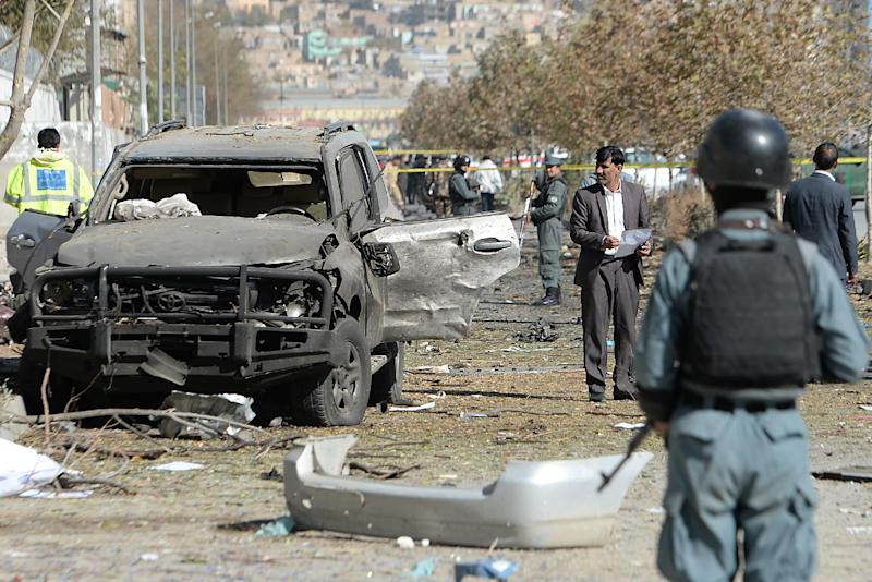 Afghan investigators inspect wreckage at the site where a suicide bomber targeted a vehicle convoy of lawmakers in Kabul on November 16, 2014 (AFP Photo/Shah Marai)
