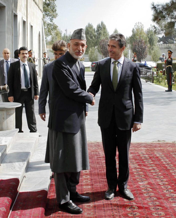 NATO's Secretary General Anders Fogh Rasmussen, right, shakes hand with Afghan President Hamid Karzai after his arrival at the presidential palace in Kabul, Afghanistan, Thursday, Oct. 18, 2012. NATO's top official said Thursday the alliance remains committed to help enable Afghan forces assume full responsibility for the country's security after 2014, when coalition troops are due to end their combat mission. (AP Photo/Omar Sobhani, Pool)