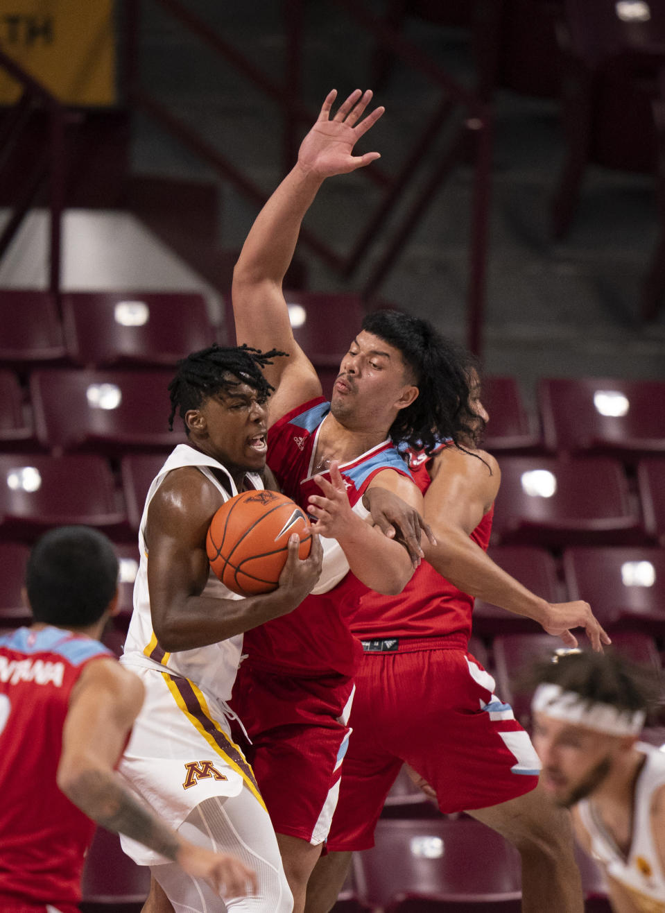 Minnesota guard Marcus Carr, center left, comes down with a defensive rebound in front of Loyola Marymount forward Keli Leaupepe, center right, in the first half of an NCAA college basketball game Monday, Nov. 30, 2020, in Minneapolis. (Jeff Wheeler/Star Tribune via AP)