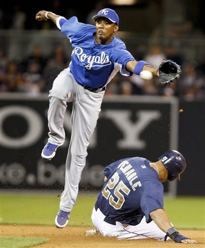 Kansas City Royals shortstop Alcides Escobar can't reach a wild throw as San Diego Padres' Will Venable slides in with a stolen base in the fifth inning of an exhibition baseball game Tuesday, April 3, 2012 in San Diego. Venable went to third on the errant throw. (AP Photo/Lenny Ignelzi)
