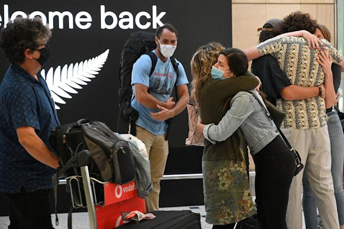 Family members embrace each other at Sydney International Airport