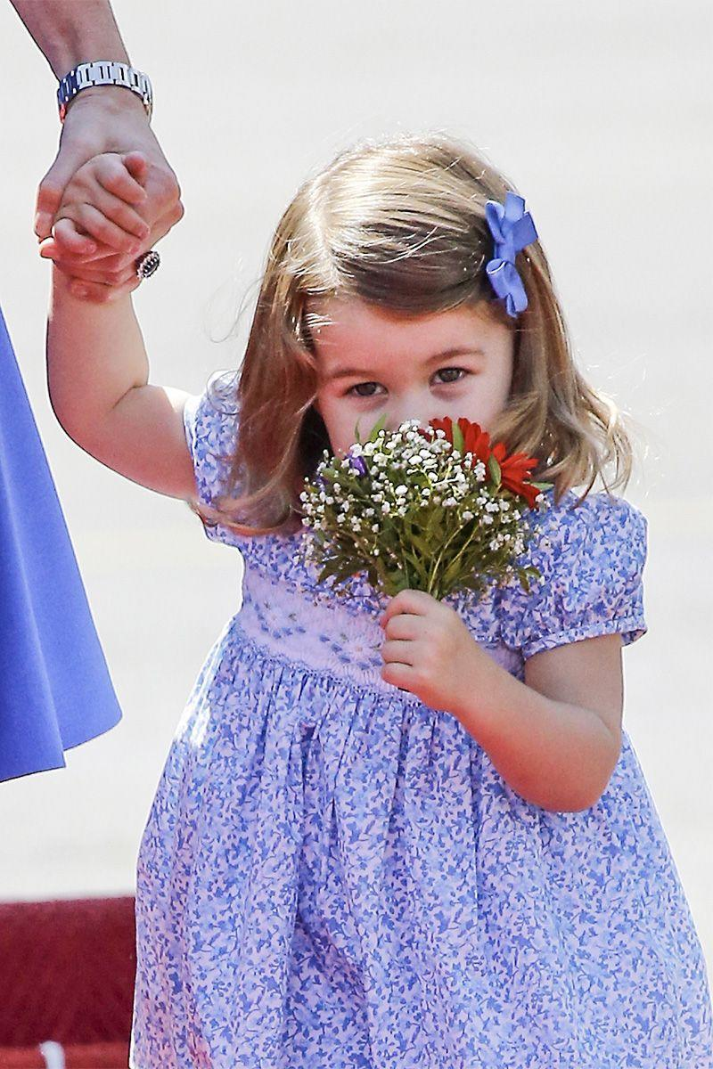 <p>...While Princess Charlotte sweetly smells flowers gifted by an onlooker.</p>