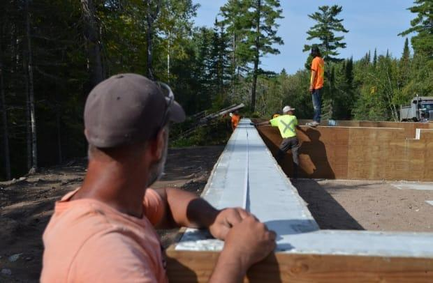 Construction workers are busy getting the foundations ready for a number of new housing units to be installed in Wauzhushk Onigum Nation, a First Nation with about 400 people living on reserve next to Kenora, Ont. There are longtime concerns over housing availability and affordability on Canadian First Nations that some say the federal parties haven't addressed. (Logan Turner/CBC - image credit)