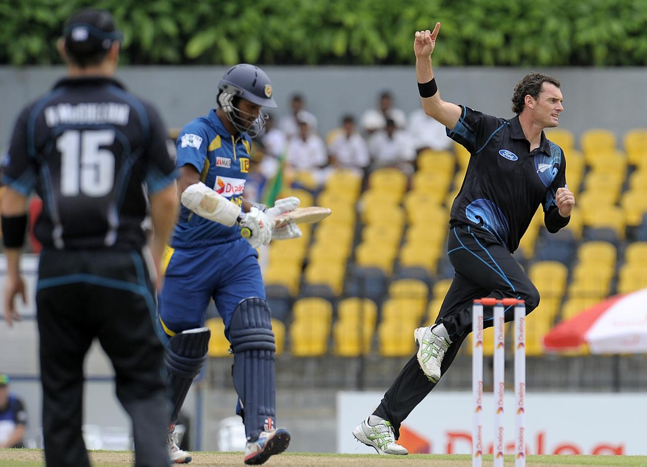New Zealand captain Kyle Mills (R) celebrates after he dismissed Sri Lankan batsman Dimuth Karunaratne (C) during the second One Day International (ODI) cricket match between Sri Lanka and New Zealand at the Suriyawewa Mahinda Rajapakse International Cricket Stadium in the southern district of Hambantota on November 12, 2013. AFP PHOTO/ LAKRUWAN WANNIARACHCHI        (Photo credit should read LAKRUWAN WANNIARACHCHI/AFP/Getty Images)