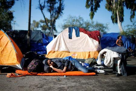 A migrant, part of a caravan of thousands from Central America trying to reach the United States, shelters as he rests on a street in Tijuana, Mexico, December 7, 2018. REUTERS/Mohammed Salem