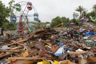 People collect usable items in debris, following Saturday's tsunami in Sumur, Indonesia, Tuesday, Dec. 25, 2018. The Christmas holiday was somber with prayers for tsunami victims in the Indonesian region hit by waves that struck without warning Saturday night.(AP Photo/Tatan Syuflana)