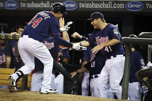 Minnesota Twins' Trevor Plouffe is congratulated in the dugout by teammates, including Drew Butera (41), after a two-run home run against the Seattle Mariners in the fourth inning of a baseball game, Wednesday, Aug. 29, 2012, in Minneapolis. (AP Photo/The Star Tribune, Renee Jones Schneider) MANDATORY CREDIT; ST. PAUL PIONEER PRESS OUT; MAGS OUT; TWIN CITIES TV OUT