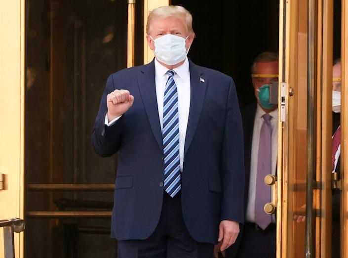 President Donald Trump makes a fist as he walks out the front doors of Walter Reed National Military Medical Center after a fourth day of treatment for the coronavirus disease (COVID-19) while returning to the White House in Washington from the hospital in Bethesda, Maryland, U.S., October 5, 2020. (Jonathan Ernst/Reuters)