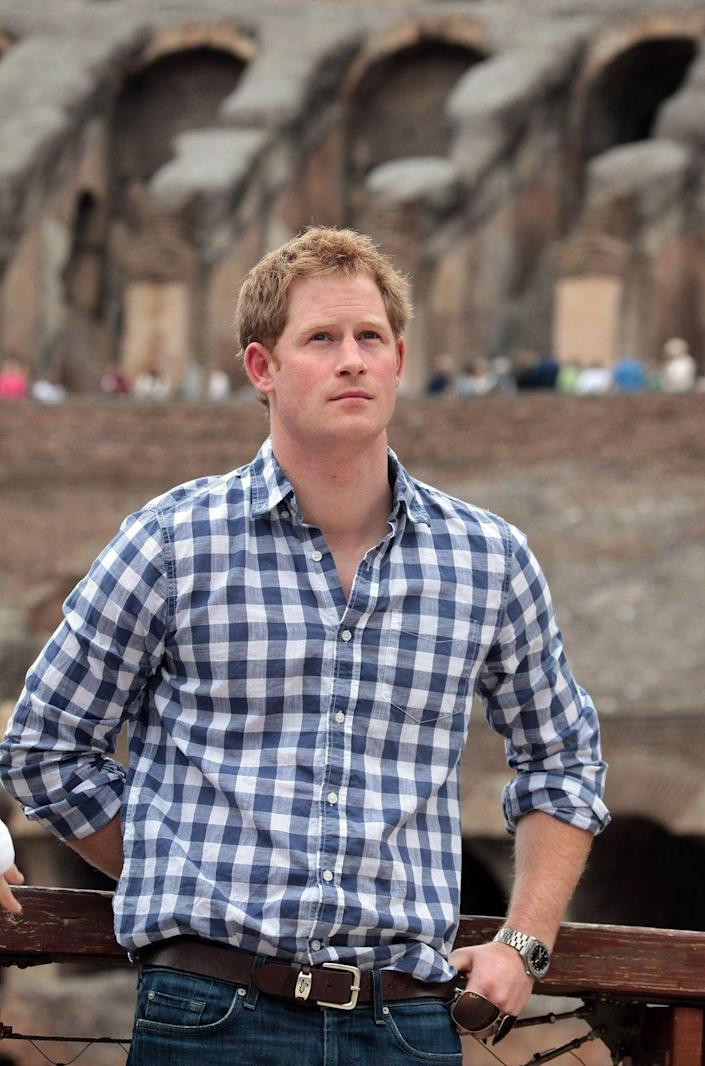 <p>Harry finds himself in a crisp gingham shirt while taking in the sights of the Colosseum in Rome. Note that the beard did not make the trip (but not to worry, it would return the following year).</p>