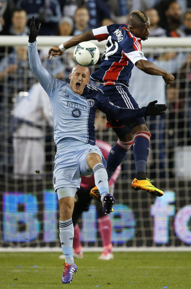 Sporting Kansas City defender Aurelien Collin, left, and New England Revolution forward Dimitry Imbongo (92) go up for the ball in front of the Sporting KC net during the first half of an MLS playoff soccer match in Kansas City, Kan., Wednesday, Nov. 6, 2013. (AP Photo/Orlin Wagner)