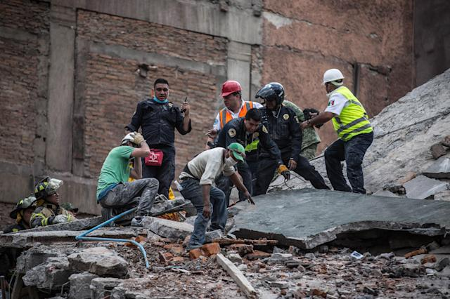 <p>Rescue workers search for the trapped citizens over the collapsed buildings after a powerful magnitude 7.1 earthquake that hit Mexico City, Mexico on Sept. 20, 2017. (Photo: Daniel Cardenas/Anadolu Agency/Getty Images) </p>