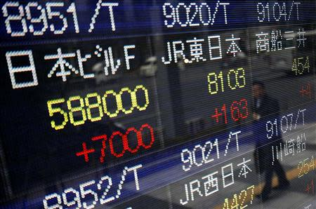 A pedestrian is reflected in an electronic board showing stock prices outside a brokerage in Tokyo