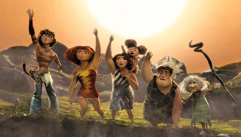 """This film publicity image released by DreamWorks Animation shows, from left, Belt the sloth, voiced by Chris Sanders, Guy, voiced by Ryan Reynolds, Eep, voiced by Emma Stone, Ugga, voiced by Catherine Keener, holding Sandy, voiced by Randy Thom, Thunk, voiced by Clark Duke, Gran, voiced by Cloris Leachman, in a scene from """"The Croods."""" (AP Photo/DreamWorks Animation)"""